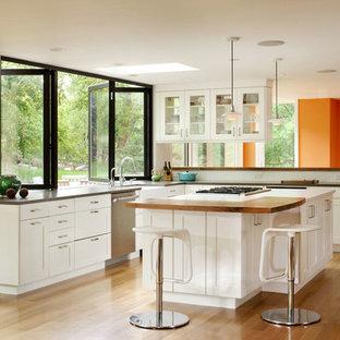 Klassische Küche mit Arbeitsplatte aus Holz, Schrankfronten im Shaker-Stil, weißen Schränken, Küchenrückwand in Weiß und Küchengeräten aus Edelstahl in Denver