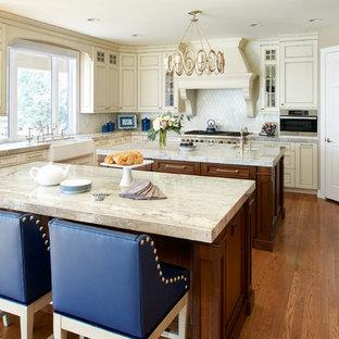 Große Klassische Küchenbar mit Landhausspüle, Schrankfronten mit vertiefter Füllung, Granit-Arbeitsplatte, Küchenrückwand in Weiß, Rückwand aus Marmor, Elektrogeräten mit Frontblende, braunem Holzboden, zwei Kücheninseln, beigen Schränken und orangem Boden in Denver