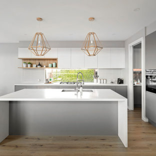 Large contemporary l-shaped kitchen in Melbourne with an undermount sink, flat-panel cabinets, grey cabinets, white splashback, porcelain splashback, panelled appliances, with island, beige floor and white benchtop.