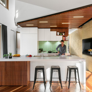 Expansive contemporary l-shaped kitchen in Melbourne with an undermount sink, flat-panel cabinets, white cabinets, green splashback, panelled appliances, medium hardwood floors, with island, brown floor, white benchtop and wood.