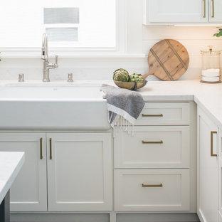 サクラメントの中サイズのヴィクトリアン調のおしゃれなキッチン (エプロンフロントシンク、シェーカースタイル扉のキャビネット、白いキャビネット、珪岩カウンター、石スラブのキッチンパネル、シルバーの調理設備の、スレートの床、グレーの床) の写真