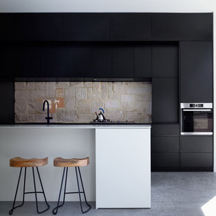 Inspiration for a contemporary kitchen in Sydney with flat-panel cabinets, black cabinets, beige splashback, stainless steel appliances, concrete floors, with island, grey floor and white benchtop.
