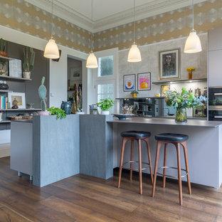 На фото: кухни среднего размера в стиле фьюжн с плоскими фасадами, серыми фасадами, коричневым полом, серым фартуком, черной техникой и темным паркетным полом