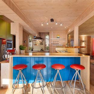 Idées déco pour une cuisine bord de mer en U avec un évier 2 bacs, un placard à porte plane, un plan de travail en bois, une crédence jaune, une crédence en carreau de céramique, un électroménager en acier inoxydable, un îlot central et un sol en bois clair.