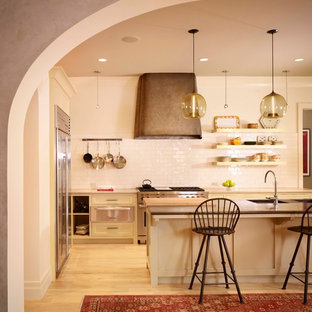 Inspiration for a mediterranean kitchen in Austin with shaker cabinets, beige cabinets, white splashback, subway tile splashback, stainless steel appliances, light hardwood floors and with island.