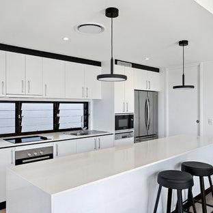 Inspiration pour une cuisine ouverte parallèle ethnique de taille moyenne avec un évier 1 bac, un plan de travail en quartz modifié, une crédence blanche, une crédence en fenêtre, un électroménager en acier inoxydable, un sol en ardoise, un îlot central, un sol gris et un plan de travail blanc.