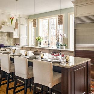 Große Klassische Küche in L-Form mit Unterbauwaschbecken, Schrankfronten mit vertiefter Füllung, weißen Schränken, Granit-Arbeitsplatte, Küchenrückwand in Grau, Rückwand aus Glasfliesen, Küchengeräten aus Edelstahl, hellem Holzboden, Kücheninsel, braunem Boden und beiger Arbeitsplatte in Boston