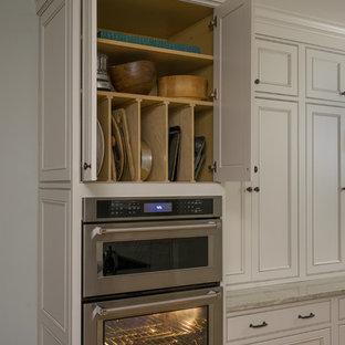 ボストンの大きいトラディショナルスタイルのおしゃれなキッチン (アンダーカウンターシンク、落し込みパネル扉のキャビネット、白いキャビネット、御影石カウンター、グレーのキッチンパネル、ガラスタイルのキッチンパネル、シルバーの調理設備の、淡色無垢フローリング、茶色い床) の写真
