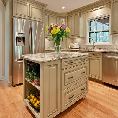 Mid-sized elegant l-shaped light wood floor and brown floor eat-in kitchen photo in Atlanta with raised-panel cabinets, stainless steel appliances, an undermount sink, green cabinets, granite countertops, beige backsplash, stone tile backsplash, an island and beige countertops