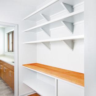 デトロイトの中サイズのコンテンポラリースタイルのおしゃれなキッチン (フラットパネル扉のキャビネット、グレーのキャビネット、木材カウンター、無垢フローリング、アイランドなし、茶色い床) の写真