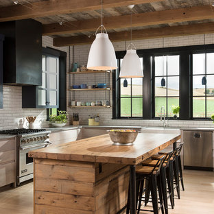 Inspiration for a large country l-shaped kitchen in Other with a farmhouse sink, flat-panel cabinets, light wood cabinets, concrete benchtops, white splashback, subway tile splashback, stainless steel appliances, light hardwood floors and with island.