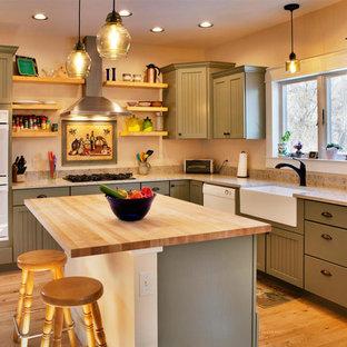 他の地域の中くらいのおしゃれなキッチン (エプロンフロントシンク、シェーカースタイル扉のキャビネット、緑のキャビネット、無垢フローリング、茶色い床、白い調理設備、ベージュのキッチンカウンター) の写真