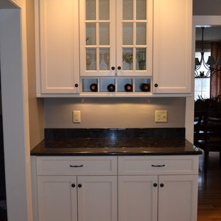 Large traditional eat-in kitchen remodeling - Example of a large classic u-shaped light wood floor eat-in kitchen design in Boston with a single-bowl sink, recessed-panel cabinets, white cabinets, granite countertops, white backsplash, subway tile backsplash, stainless steel appliances and an island