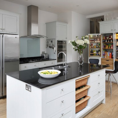 Mid-sized transitional single-wall medium tone wood floor open concept kitchen photo in London with a drop-in sink, shaker cabinets, white cabinets, granite countertops, glass sheet backsplash, stainless steel appliances, an island and black countertops