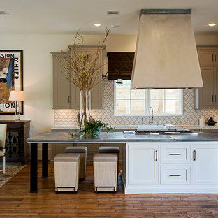 Design ideas for a mid-sized transitional l-shaped open plan kitchen in Houston with a farmhouse sink, shaker cabinets, grey cabinets, zinc benchtops, porcelain splashback, stainless steel appliances, medium hardwood floors, with island and white splashback.