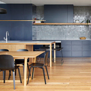 This is an example of a contemporary galley eat-in kitchen in Melbourne with an undermount sink, flat-panel cabinets, grey splashback, panelled appliances, light hardwood floors, with island, white benchtop, grey cabinets and brown floor.