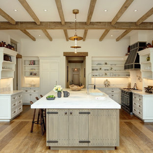 Farmhouse kitchen designs - Inspiration for a cottage light wood floor kitchen remodel in Boston with a farmhouse sink, open cabinets, white cabinets, white backsplash, black appliances, an island and white countertops