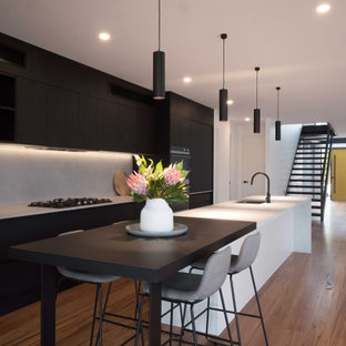 Design ideas for a large contemporary kitchen in Melbourne with an undermount sink, black cabinets, grey splashback, black appliances, medium hardwood floors, with island, brown floor and grey benchtop.