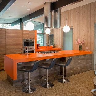 Inspiration for a midcentury galley eat-in kitchen in Austin with an undermount sink, flat-panel cabinets, medium wood cabinets, stainless steel appliances and orange benchtop.