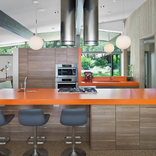 Mid-sized mid-century modern open concept kitchen designs - Mid-sized 1960s galley brown floor open concept kitchen photo in Austin with an undermount sink, flat-panel cabinets, medium tone wood cabinets, stainless steel appliances, an island, quartz countertops and orange countertops