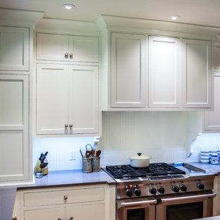 Modelo de cocina en L, romántica, grande, abierta, con fregadero bajoencimera, armarios estilo shaker, puertas de armario blancas, encimera de cuarzo compacto, salpicadero blanco, electrodomésticos de acero inoxidable, suelo de madera clara y una isla