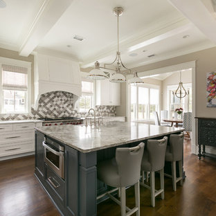 Coastal eat-in kitchen ideas - Inspiration for a coastal dark wood floor and brown floor eat-in kitchen remodel in Charleston with an island, shaker cabinets, white cabinets, multicolored backsplash, stainless steel appliances and gray countertops