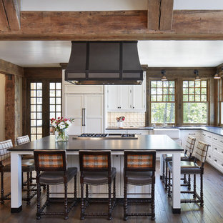 Large coastal open concept kitchen ideas - Example of a large beach style l-shaped medium tone wood floor and brown floor open concept kitchen design in Minneapolis with white cabinets, white backsplash, porcelain backsplash, paneled appliances, an island, a farmhouse sink, shaker cabinets and solid surface countertops