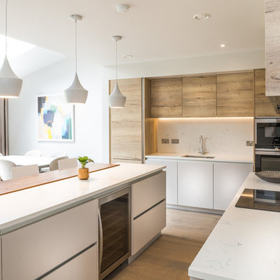 Inspiration for a mid-sized contemporary galley light wood floor open concept kitchen remodel in Other with a single-bowl sink, flat-panel cabinets, light wood cabinets, quartzite countertops, white backsplash, stone slab backsplash, stainless steel appliances and an island