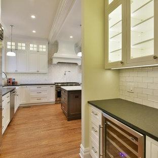 ニューヨークの大きいヴィクトリアン調のおしゃれなキッチン (エプロンフロントシンク、インセット扉のキャビネット、白いキャビネット、クオーツストーンカウンター、白いキッチンパネル、セラミックタイルのキッチンパネル、シルバーの調理設備の、無垢フローリング) の写真