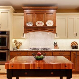 Idéer för mellanstora vintage beige kök, med en rustik diskho, skåp i shakerstil, gula skåp, granitbänkskiva, vitt stänkskydd, stänkskydd i porslinskakel, rostfria vitvaror, mellanmörkt trägolv, en köksö och brunt golv