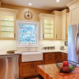 アトランタの広いトラディショナルスタイルのおしゃれなキッチン (エプロンフロントシンク、シェーカースタイル扉のキャビネット、黄色いキャビネット、御影石カウンター、白いキッチンパネル、磁器タイルのキッチンパネル、シルバーの調理設備、無垢フローリング、茶色い床、ベージュのキッチンカウンター) の写真