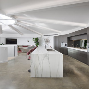 Expansive contemporary galley kitchen in Perth with a double-bowl sink, flat-panel cabinets, tile benchtops, concrete floors, with island, grey floor, grey cabinets, stainless steel appliances, white benchtop and exposed beam.