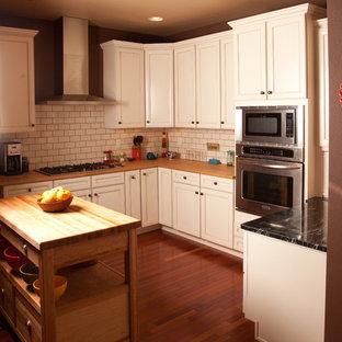 Klassisk inredning av ett kök, med stänkskydd i tunnelbanekakel och rostfria vitvaror