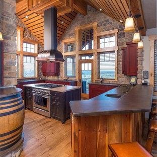 Diseño de cocina en U, rural, grande, con puertas de armario rojas, electrodomésticos de acero inoxidable, suelo de madera en tonos medios, armarios estilo shaker, encimera de acrílico, salpicadero marrón, salpicadero de azulejos de piedra y una isla