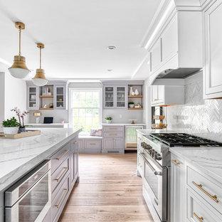 Inredning av ett klassiskt stort vit vitt kök, med en undermonterad diskho, luckor med profilerade fronter, vita skåp, bänkskiva i kvarts, vitt stänkskydd, stänkskydd i mosaik, integrerade vitvaror och en köksö