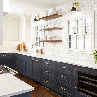 Mittelgroße Klassische Küche mit Schrankfronten im Shaker-Stil, blauen Schränken, Quarzwerkstein-Arbeitsplatte, Küchenrückwand in Weiß, Rückwand aus Keramikfliesen, Elektrogeräten mit Frontblende, dunklem Holzboden, braunem Boden, Waschbecken und weißer Arbeitsplatte in Minneapolis