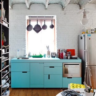 Einzeilige Industrial Küche mit flächenbündigen Schrankfronten, Küchengeräten aus Edelstahl, türkisfarbenen Schränken und türkiser Arbeitsplatte