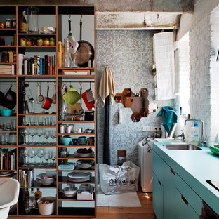 This is an example of an industrial single-wall open plan kitchen with open cabinets, blue cabinets and turquoise benchtop.