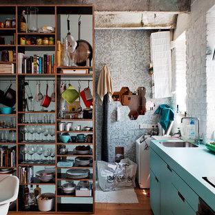 Foto di una cucina industriale con nessun'anta, ante blu e top turchese