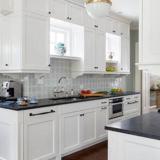 Immagine di una cucina chic con lavello sottopiano, ante in stile shaker, ante bianche, paraspruzzi blu, paraspruzzi con piastrelle di vetro, elettrodomestici in acciaio inossidabile e parquet scuro