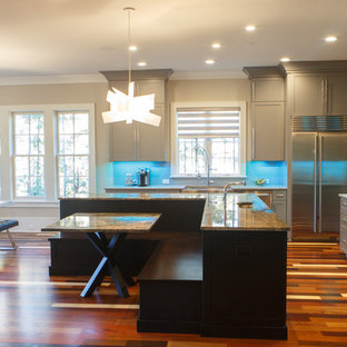 This is an example of a mid-sized modern l-shaped eat-in kitchen in Charlotte with a farmhouse sink, recessed-panel cabinets, grey cabinets, granite benchtops, white splashback, metal splashback, stainless steel appliances, light hardwood floors, with island, multi-coloured floor and brown benchtop.