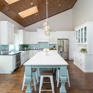 Klassische Küche mit Landhausspüle, Schrankfronten im Shaker-Stil, weißen Schränken, Quarzwerkstein-Arbeitsplatte, Küchenrückwand in Blau, Rückwand aus Metrofliesen, Küchengeräten aus Edelstahl, dunklem Holzboden und Kücheninsel in Kansas City