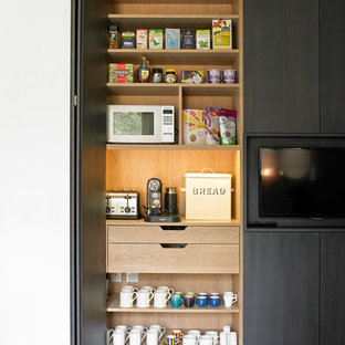 Design ideas for a contemporary kitchen pantry in London with flat-panel cabinets, black cabinets and porcelain floors.