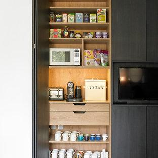 Moderne Küche mit Vorratsschrank, flächenbündigen Schrankfronten, schwarzen Schränken und Porzellan-Bodenfliesen in London