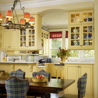 Bild på ett kök och matrum, med luckor med profilerade fronter, gula skåp, vitt stänkskydd, stänkskydd i sten, marmorbänkskiva och rostfria vitvaror