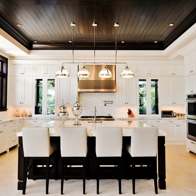 Inspiration for a timeless u-shaped kitchen remodel in Miami with paneled appliances, white cabinets, white backsplash and recessed-panel cabinets