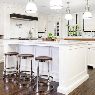 Large traditional eat-in kitchen photos - Inspiration for a large timeless u-shaped dark wood floor eat-in kitchen remodel in Cleveland with an undermount sink, beaded inset cabinets, white cabinets, marble countertops, white backsplash, ceramic backsplash, paneled appliances and two islands