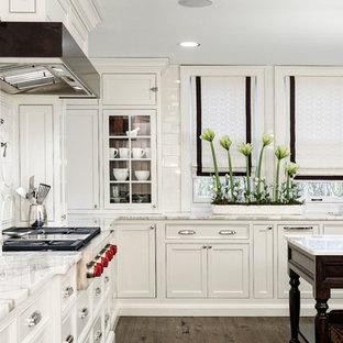 クリーブランドのトラディショナルスタイルのおしゃれなコの字型キッチン (アンダーカウンターシンク、インセット扉のキャビネット、白いキャビネット、大理石カウンター、白いキッチンパネル、セラミックタイルのキッチンパネル、パネルと同色の調理設備、濃色無垢フローリング) の写真