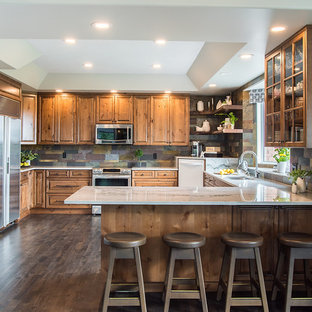 This is an example of a large country u-shaped eat-in kitchen in Edmonton with a double-bowl sink, raised-panel cabinets, distressed cabinets, quartzite benchtops, multi-coloured splashback, slate splashback, stainless steel appliances, medium hardwood floors, grey floor and multi-coloured benchtop.