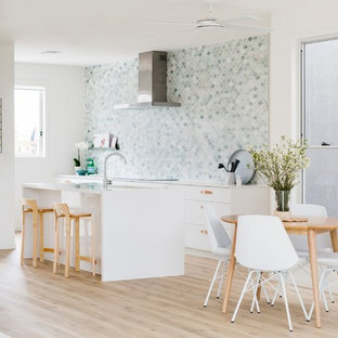 Beach style kitchen in Sunshine Coast with granite benchtops, marble splashback, stainless steel appliances and with island.